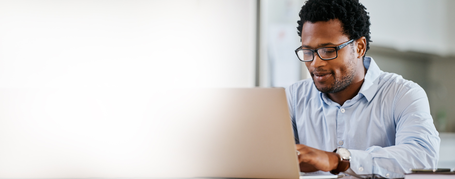 man in blue shirt using laptop to estimate health care costs