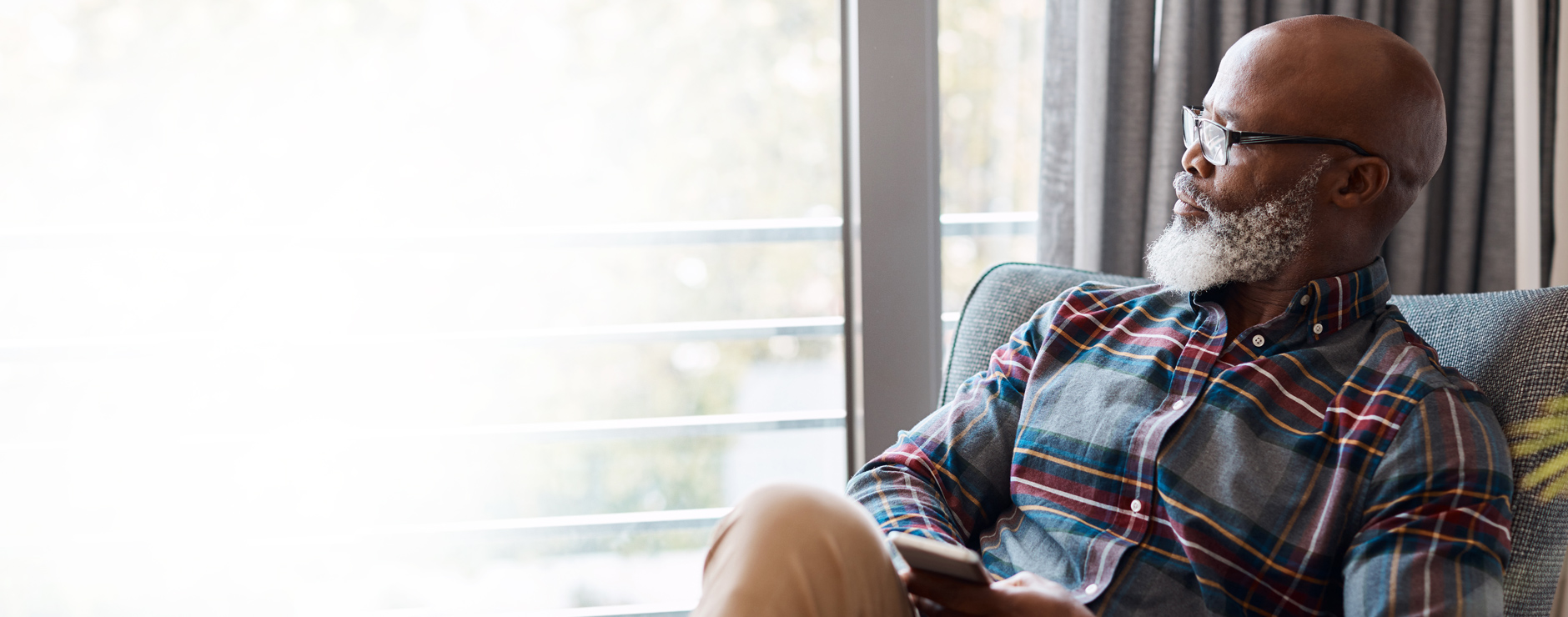 man in plaid shirt sitting in chair preparing to schedule colorectal cancer screening