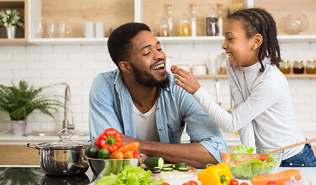 young daughter and dad prepare healthy meal on a tight budget at home