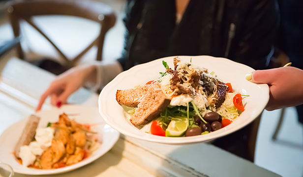 Restaurant server delivers two plates filled with healthy food to a table