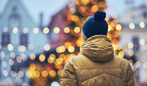 rear view of man in warm clothing viewing holiday lights