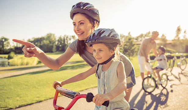 mom and young daughter wearing bike helmets prepare to exercise on sunny day