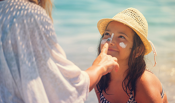 Mom applying sunscreen to daughter