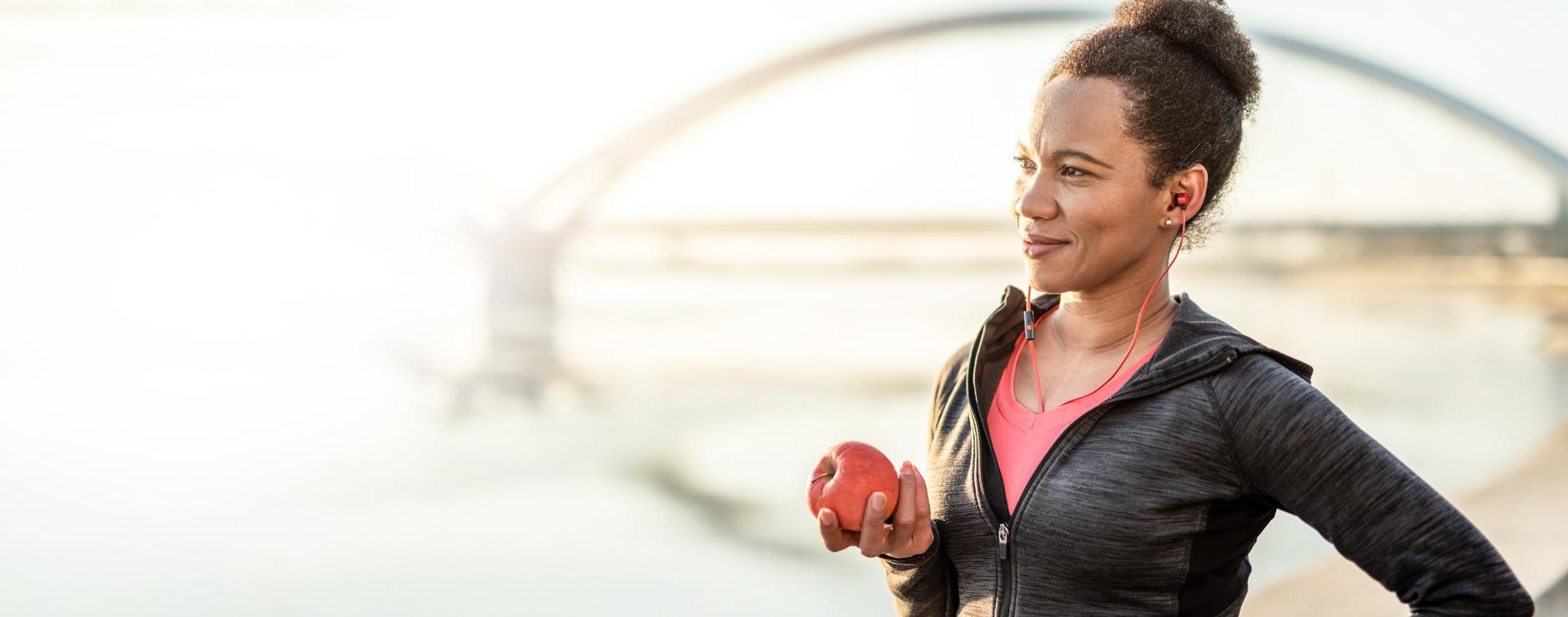 woman dressed in fitness gear holding an apple